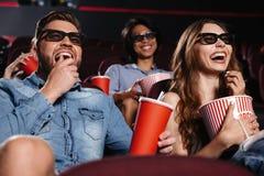 Amis riants s'asseyant en film de montre de cinéma Photo stock