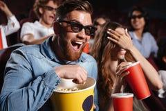 Amis riants s'asseyant en film de montre de cinéma Images stock