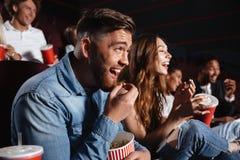 Amis riants s'asseyant en film de montre de cinéma Photographie stock