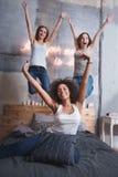 Amis riants sautant sur le lit et avoir l'amusement Photo libre de droits