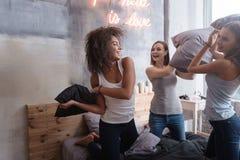 Amis riants se tenant sur le lit et avoir le combat d'oreiller Photographie stock