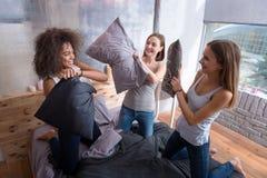 Amis riants se tenant sur le lit et avoir le combat d'oreiller Photo stock