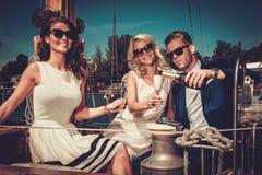Amis riches élégants ayant l'amusement sur un yacht de luxe Image stock