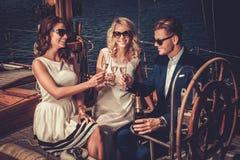 Amis riches élégants ayant l'amusement sur un yacht de luxe Photos libres de droits