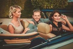 Amis riches dans le convertible classique Image stock
