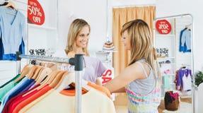 Amis rougeoyants choisissant les vêtements colorés Image stock