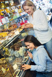 Amis sélectionnant les chocolats et la confiserie fins à la DISP de café Photo libre de droits