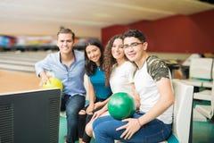 Amis sûrs avec des boules de bowling se reposant dans le club Photographie stock