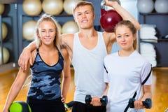 Amis sûrs soulevant des poids dans le gymnase Photos stock