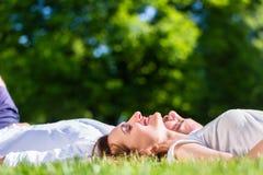 Amis s'étendant côte à côte sur la pelouse de parc Photo stock