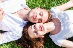 Amis s'étendant côte à côte sur le parc appréciant le soleil Images libres de droits