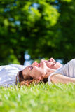 Amis s'étendant côte à côte sur le parc appréciant le soleil Photos libres de droits