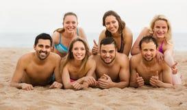 Amis s'étendant sur le sable à la plage Images libres de droits