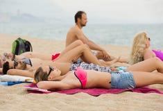 Amis s'étendant sur le sable à la plage Photos libres de droits