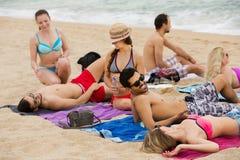 Amis s'étendant sur le sable à la plage Photographie stock