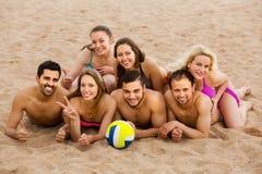 Amis s'étendant sur le sable à la plage Photo libre de droits