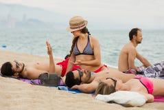 Amis s'étendant sur le sable à la plage Photographie stock libre de droits