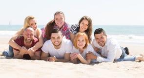 Amis s'étendant sur le sable Photographie stock libre de droits