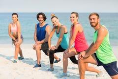 Amis s'étirant sur le rivage à la plage Image stock