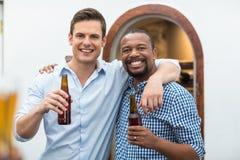 Amis s'étreignant tout en tenant des bouteilles à bière Photographie stock libre de droits