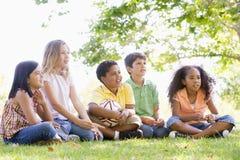Amis s'asseyant à l'extérieur avec la bille de football Image libre de droits