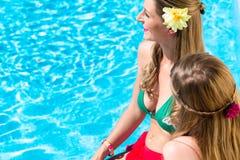 Amis s'asseyant à la piscine Image libre de droits