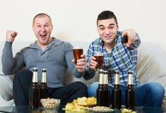 Amis s'asseyant à la table avec de la bière Photos stock