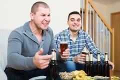 Amis s'asseyant à la table avec de la bière Images libres de droits