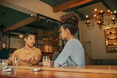 Amis s'asseyant à un couner de barre appréciant des boissons ensemble Image stock