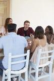 Amis s'asseyant à un dîner sur un patio, vertical Image libre de droits
