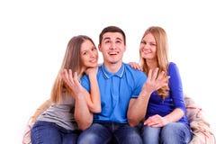 amis s'asseyant à un sofa et à une télévision de observation  Image libre de droits