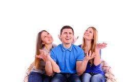 amis s'asseyant à un sofa et à une télévision de observation Image stock