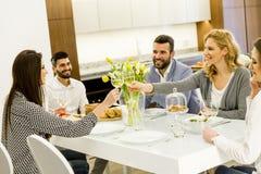 Amis s'asseyant à une table de salle à manger Image stock