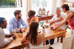 Amis s'asseyant à une table de salle à manger célébrant un anniversaire Image libre de droits