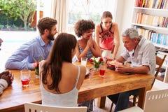 Amis s'asseyant à une table de salle à manger célébrant un anniversaire Images stock