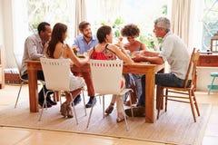 Amis s'asseyant à une table parlant pendant un dîner Image stock