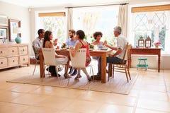 Amis s'asseyant à une table parlant pendant un dîner Photographie stock libre de droits
