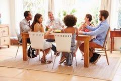 Amis s'asseyant à une table parlant pendant un dîner Photo libre de droits