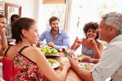 Amis s'asseyant à une table parlant pendant un dîner Images stock