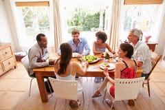 Amis s'asseyant à une table parlant pendant un dîner Photos libres de droits