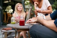 Amis s'asseyant au café extérieur jouant le jeu de carte Images libres de droits