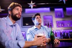 Amis s'asseyant au compteur de barre et ayant la bière Photographie stock