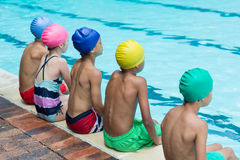 Amis s'asseyant au poolside Photo stock