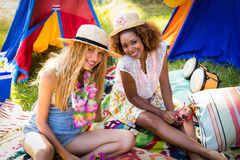 Amis s'asseyant au terrain de camping Photo libre de droits