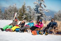 Amis s'asseyant avec des chaises de plate-forme en montagnes d'hiver sunbathing Photos stock