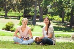 Amis s'asseyant avec leurs livres en parc Photos stock