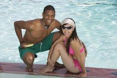 Amis s'asseyant dans la piscine Photographie stock libre de droits
