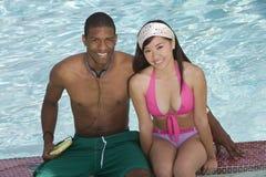 Amis s'asseyant dans la piscine Photos libres de droits