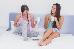 Amis s'asseyant dans le lit Image stock