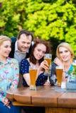 Amis s'asseyant dans le restaurant de jardin de bière Images stock